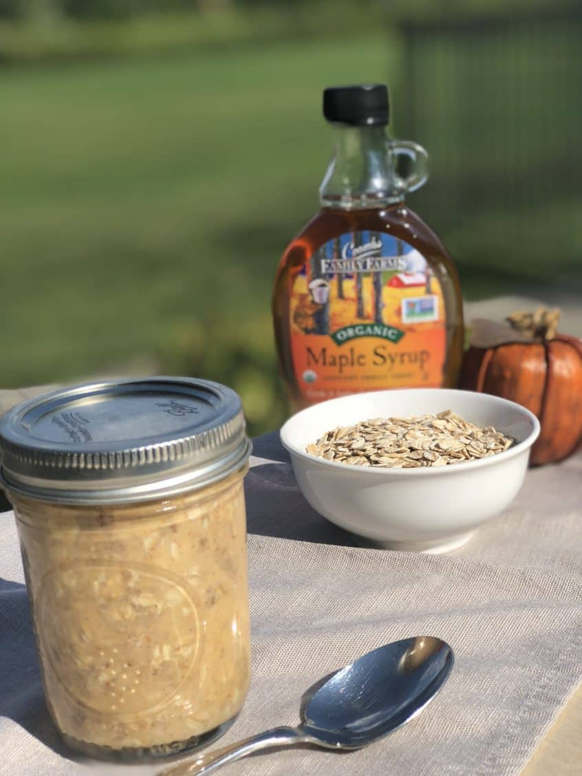 Pumpkin Pie Overnight Oats served in a mason jar with a pumpkin, uncooked oats and maple syrup on the side.
