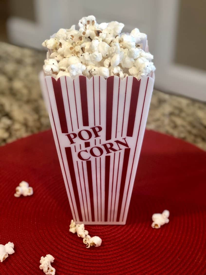 Homemade cheesy popped Popcorn in a red and white striped pop corn labeled container