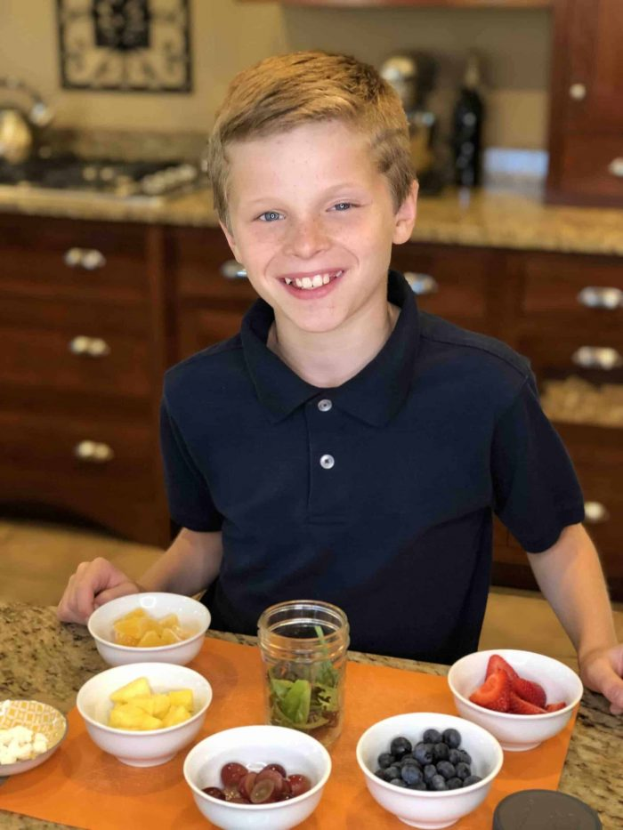 Young boy with all of the ingredients of colorful fresh fruits and veggies around him ready to build a Rainbow Salad Recipe in a jar