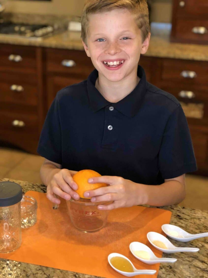 A young boy squeezing juice from a fresh navel orange into a glass measuring cup preparing to make Honey Citrus vinaigrette
