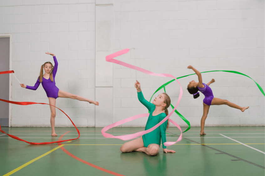 Young girls in leotards in a dance class using dancing ribbons as they dance to the music