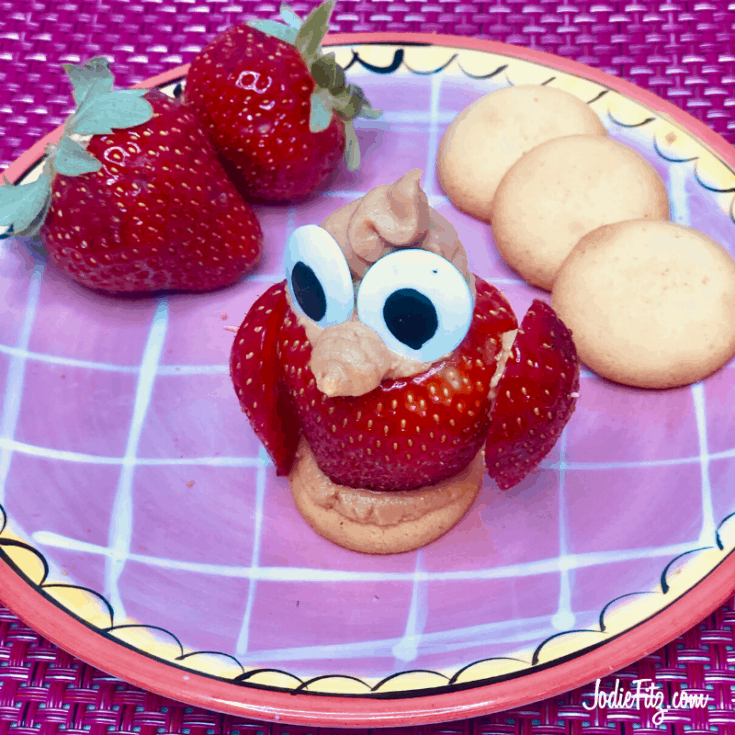 Stuffed Strawberry sitting on a Nilla wafer arranged to look like an owl, on a plate with Nilla wafers and strawberries
