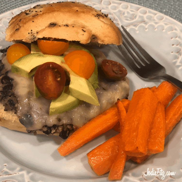Homemade black bean burger topped with cheese, avocado, and cherry tomatoes, served on a plate with carrots