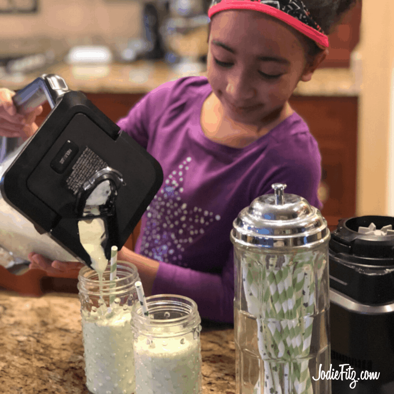 A girl pouring a shamrock shake from a blender into two glasses