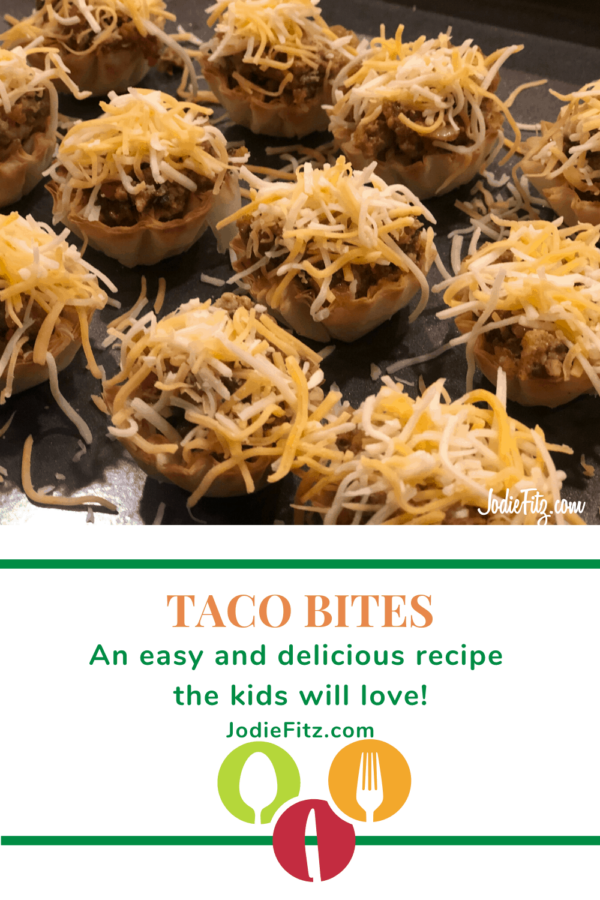 Taco bites topped with shredded cheese arranged on a baking sheet