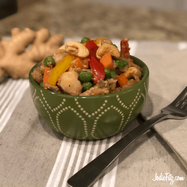 Cauliflower rice, veggie packed, chicken stir fry served in a green patterned bowl with peas, bell peppers and cashews.