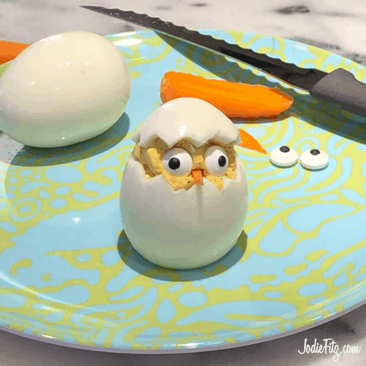 Deviled egg prepared to look like a chick peeking out of an egg with a carrot beak