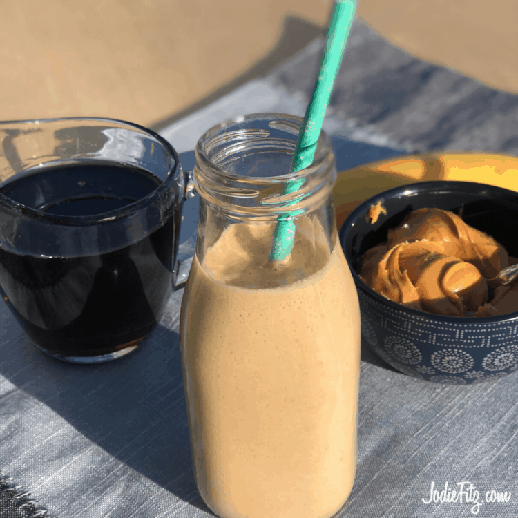Banana Nut Smoothie in a glass jar with a straw, next to a bowl of peanut butter and a cup of coffee