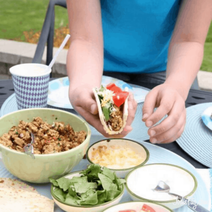 Child's hands holding a taco standing at a table with bowls of turkey, cheese, lettuce, tomatoes, and sour cream