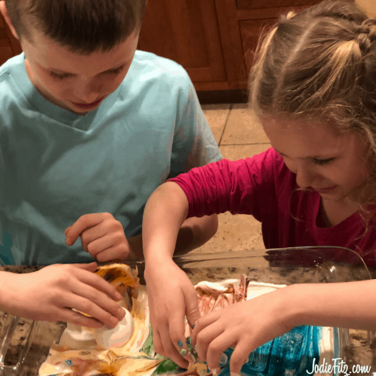 Two kids rolling eggs in a pan of dyed whipped cream