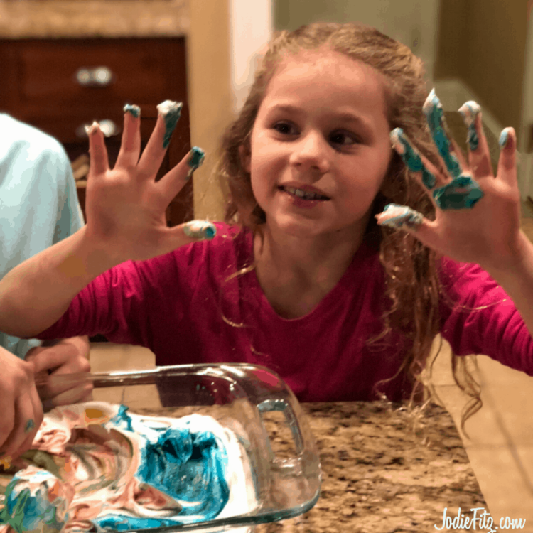 A girl smiling and holding up her dyed hands from rolling eggs in dyed whipped cream