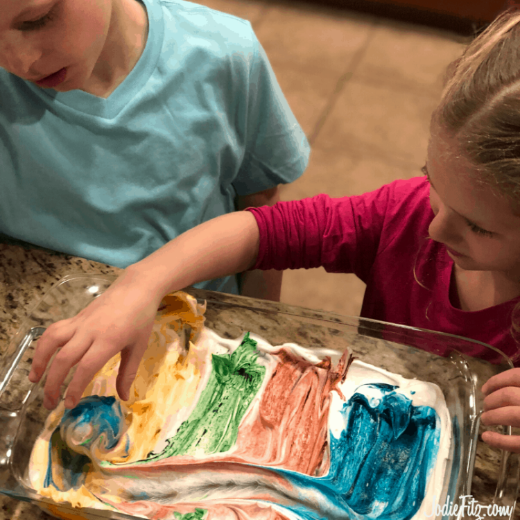 Two kids rolling an egg in a pan of dyed whipped cream