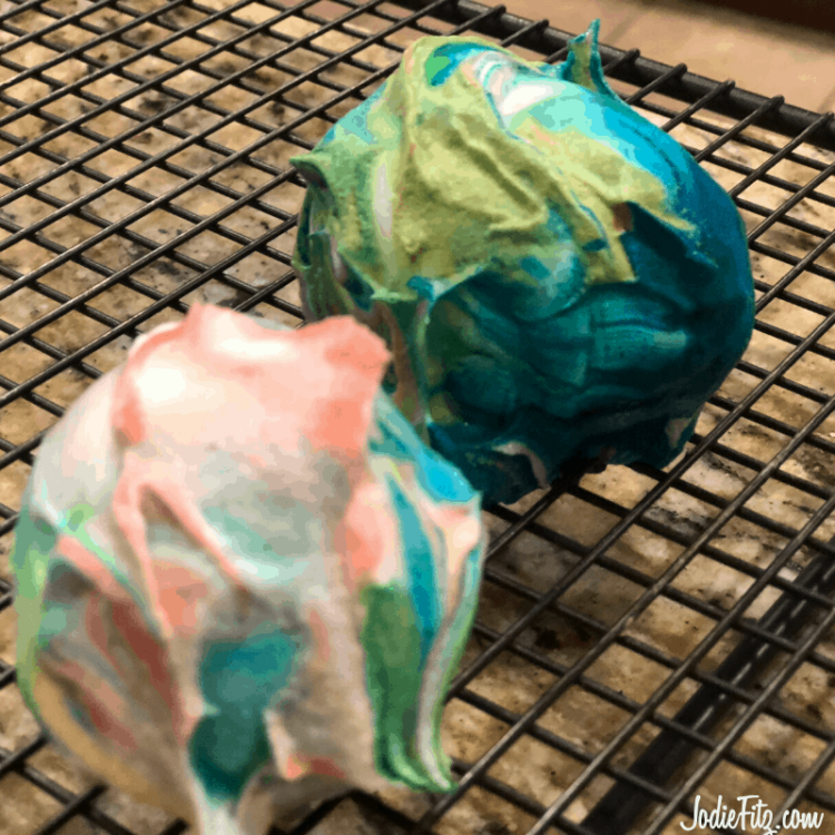 Two eggs covered with dyed whipped cream sitting on a drying rack