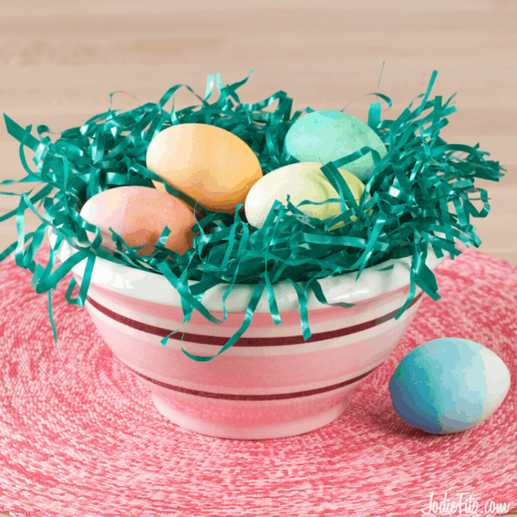 A bowl of ombre colored eggs sitting in easter grass