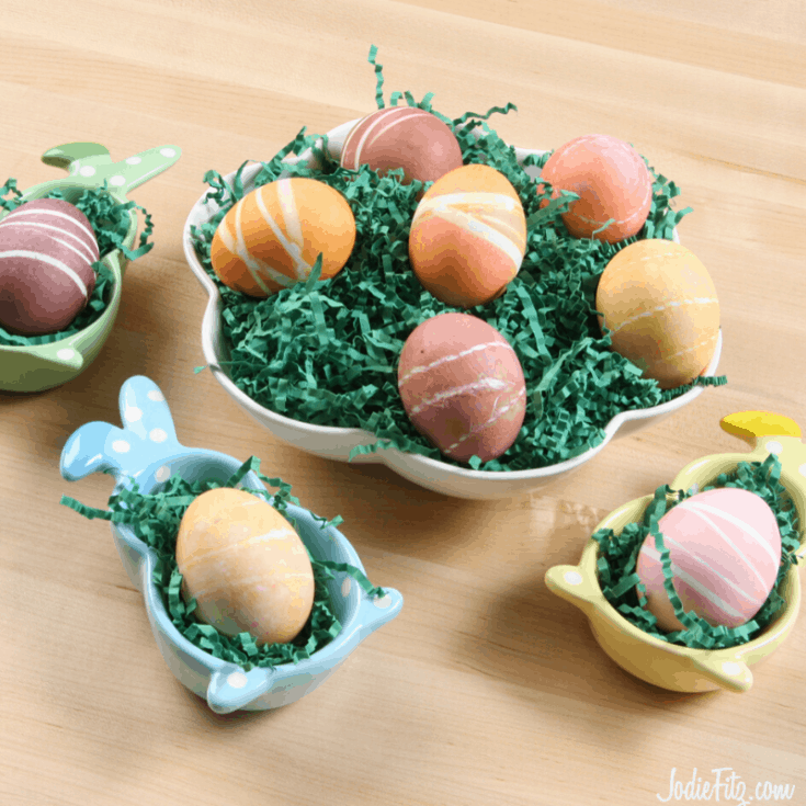 Striped easter eggs sitting in various rabbit-shaped bowls filled with easter grass