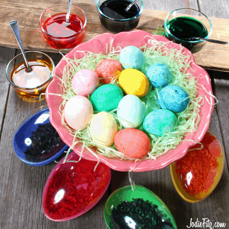 Speckled easter eggs in a bowl filled with easter grass surrounded by smaller bowls of dyed water and colored rice