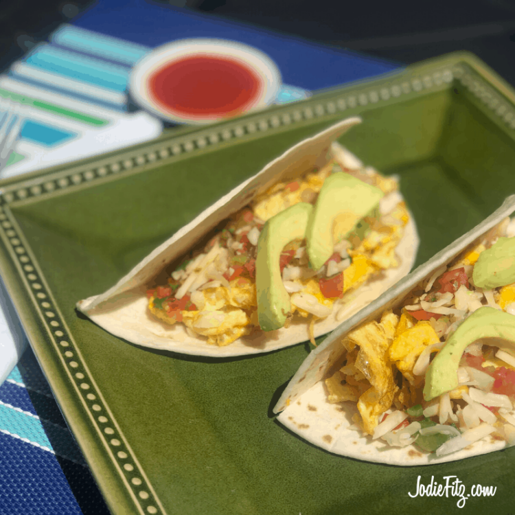 Breakfast tacos made with flour tortillas filled with seasoned scrambled eggs, pico de gallo, shredded Monterey jack cheese, topped with fresh cut slices of avocado.