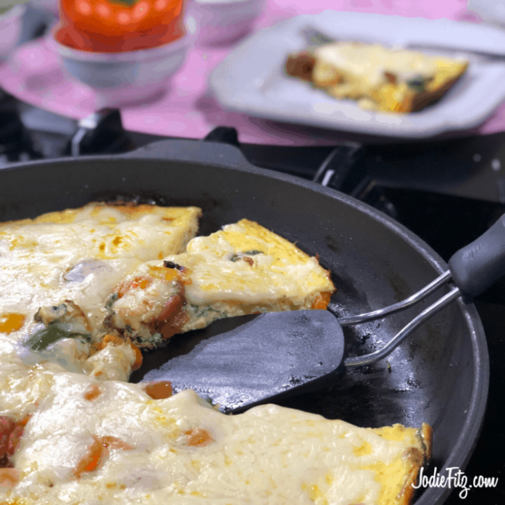 Egg Frittata in a skillet packed with fresh grape tomatoes, basil and asparagus topped with melted mozzarella cheese.