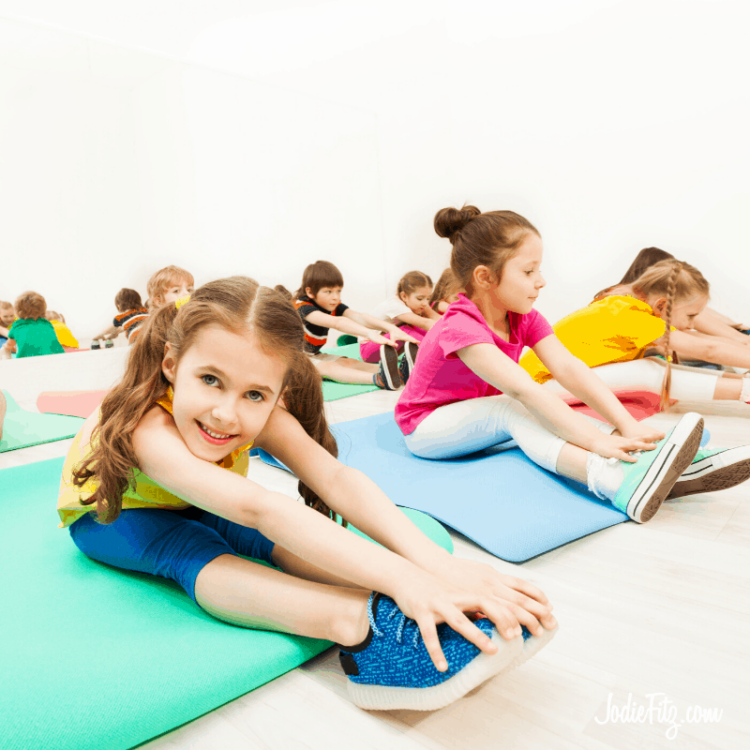 Children in an exercise class on multi colored matts wearing bright colored clothing following a class instructors directions as they reach to touch their toes.