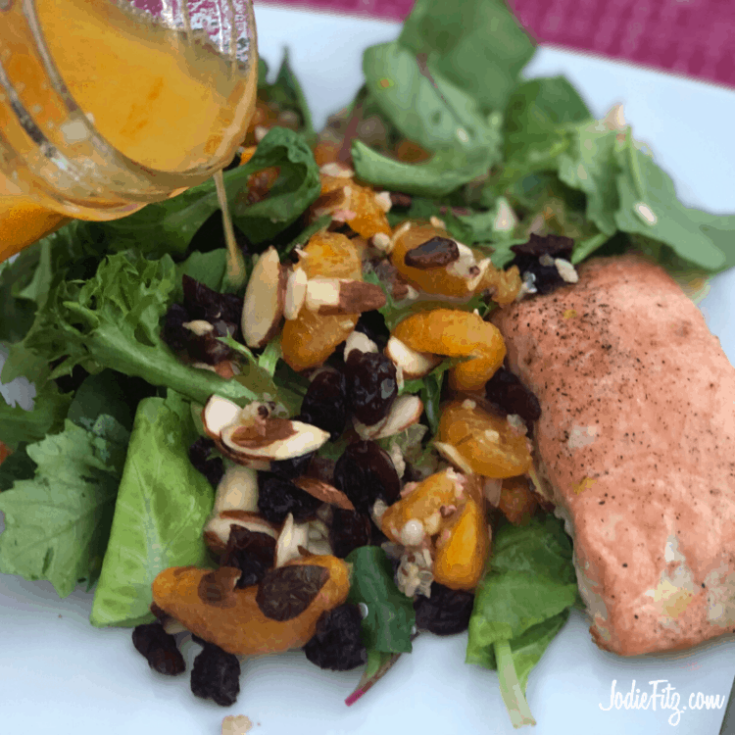 Mandarin Orange Vinaigrette being poured over a fresh salad topped with sliced almonds, craisins and mandarin orange pieces with a side of grilled, seasoned salmon.