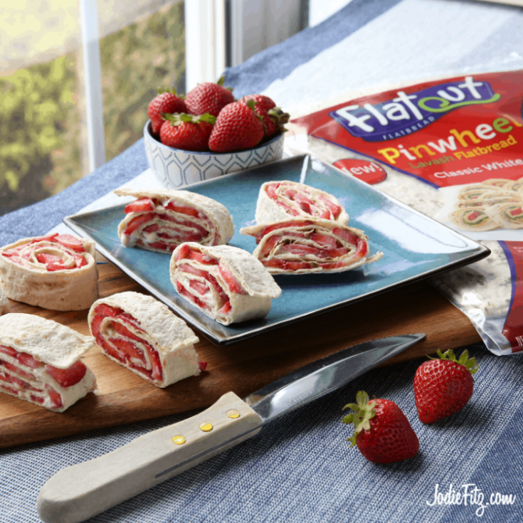 Strawberries rolled in a flatbread with sweetened cream cheese and fresh sliced strawberries and sliced to serve.