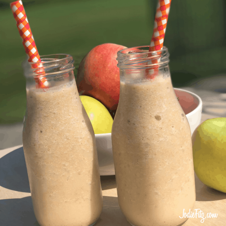 Apple Cashew Smoothie made with cashew milk served in a milk jar shaped glass served with plaid orange paper straws.