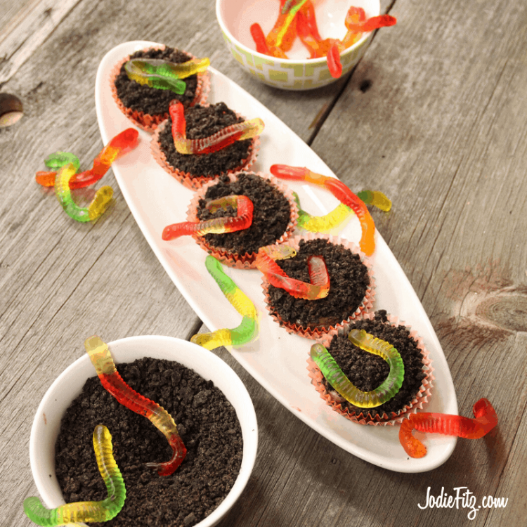 Brownie batter cooked in a cupcake tin to create a brownie bowl filled with edible dirt dessert made from pudding and crushed Oreo cookies topped with gummy worms.