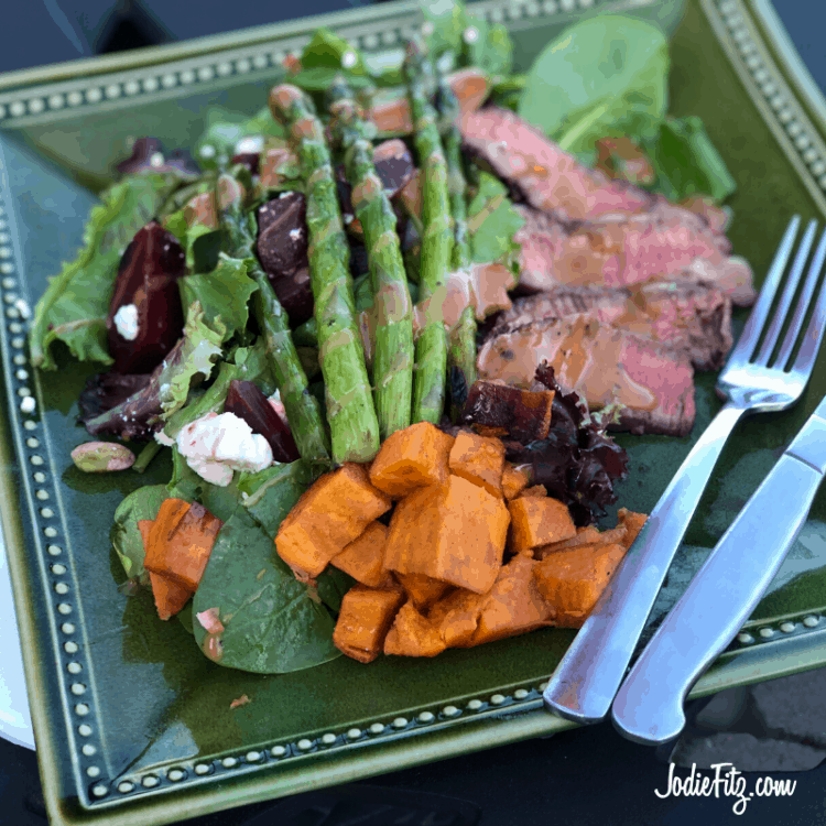 Grilled Steak with a seasoned spice rub with grilled sweet potatoes and grilled asparagus on top of a spring mix with honey goat cheese, cooked beets and pistachios.