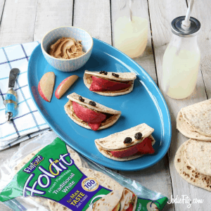 Apple wedges with peanut butter, honey, flatbread, strawberry and raisins or blueberries turned into a fruit head snack.