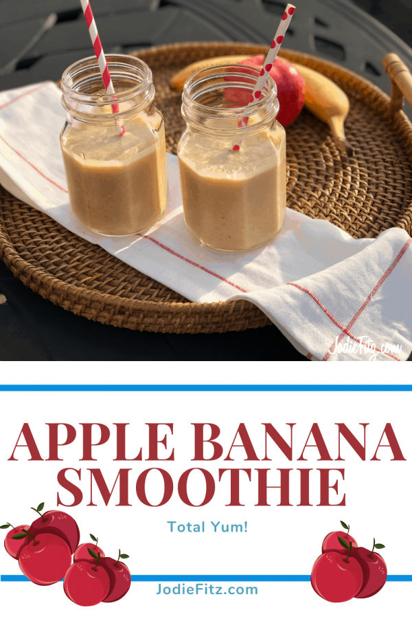 Apple banana smoothie served in glass mason jars on a wicker tray with fresh fruit