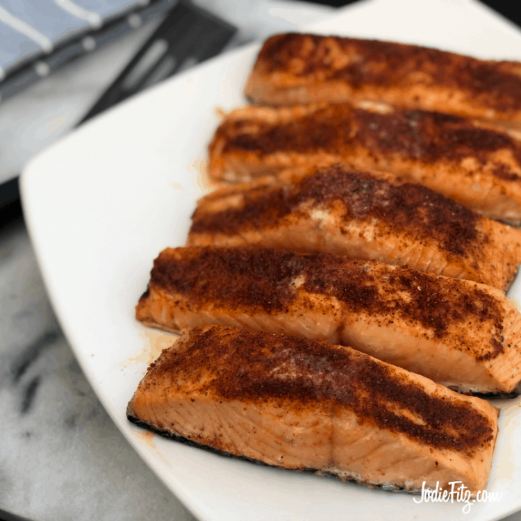 Grilled seasoned salmon with a mix of spices on top served on a white dish on a marble counter