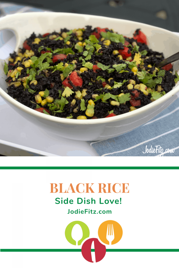 Black rice with corn kernels, dice grape tomatoes and fresh cilantro served as a side dish in a white bowl