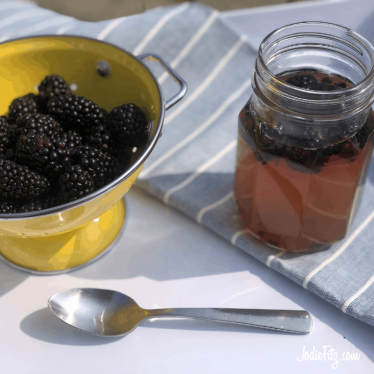 A muddled blackberry green tea served in a decorative glass mason jar served on a white tray with a blue linen napkin next to a yellow colander with fresh blackberries