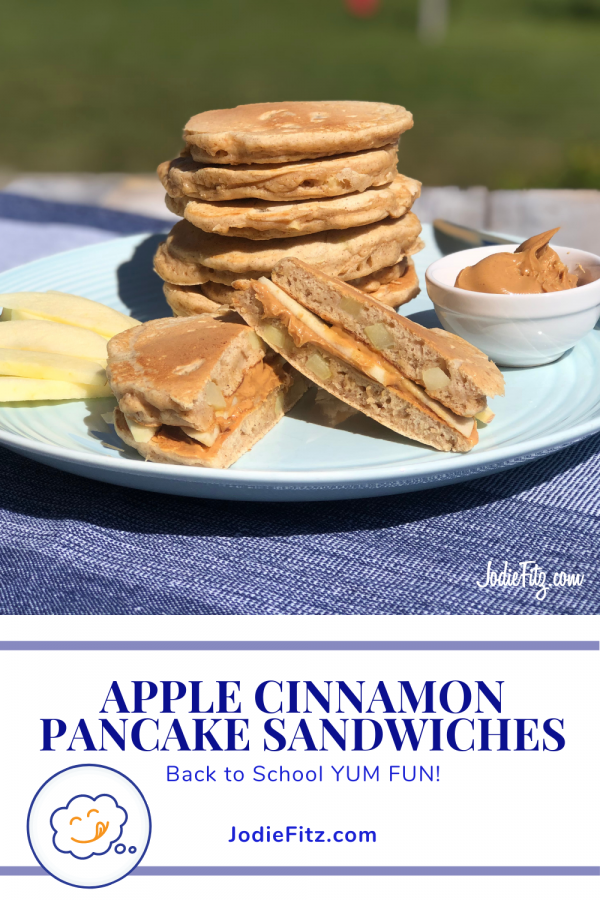 Two cinnamon apple pancake made with fresh diced apple in the batter, cooked and turned into a sandwich filled with peanut butter, honey and fresh slices of apples on a light blue plate with a dark blue runner under the plate.