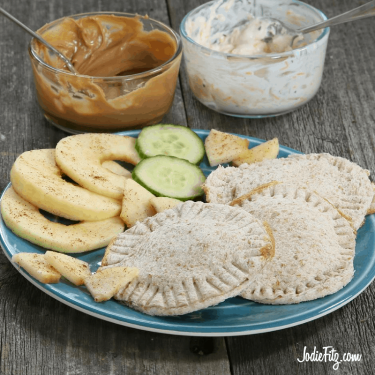 Crustless, circular sandwich pockets made with a round cookie cutter, stuffed and closed by using a fork to pinch the edges. The sandwiches are filled with a combo of peanut butter and fresh fruit or veggie cream cheese, ranch dressing and fresh veggies.
