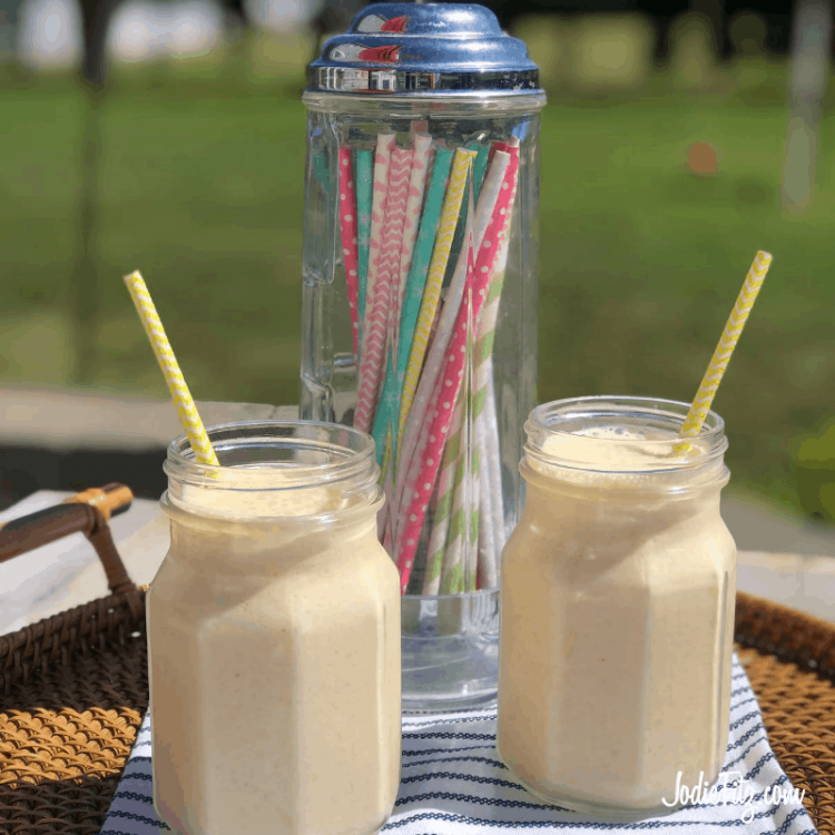 Two creamy fruit smoothies in glass jars arranged on a tray with colorful straws.