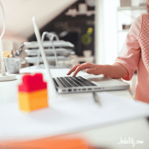 A laptop on a counter being used by a woman in a pink sweater