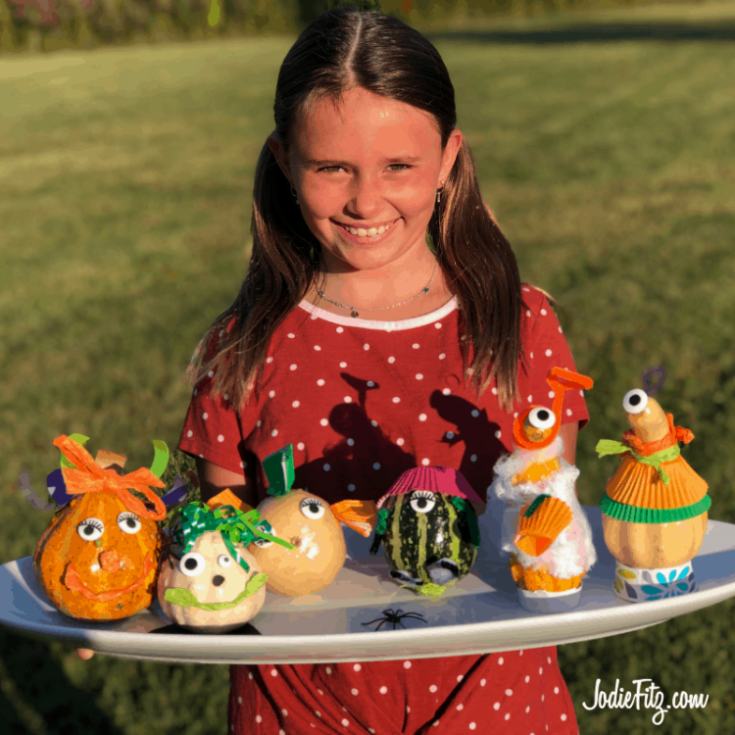 A young girl holding a white tray with six gourds that have been turned into goofy gourd crafty characters with silly eyes, construction paper, yard, tissue paper, yarn and other items