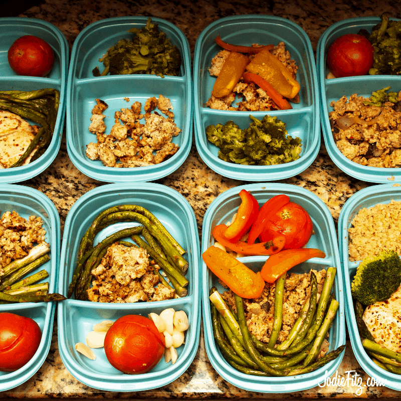 Eight containers of meals arranged on a counter for meal prepping
