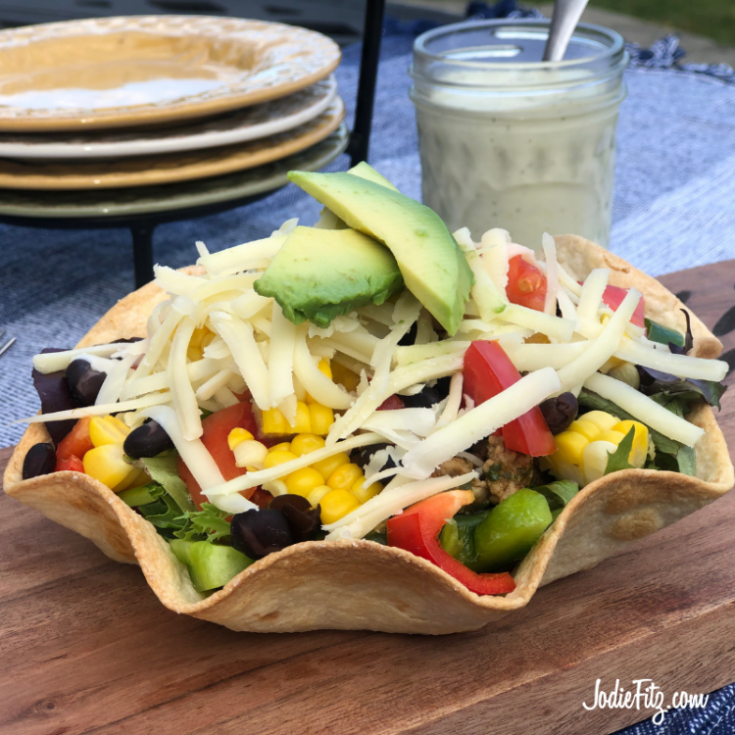 Taco Salad in a tortilla shell bowl filled with spring mix, taco meat, corn, fresh peppers and tomatoes, black beans, shredded cheese and avocados.