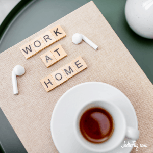 Scrabble letters spelling out 'work at home' on a placemat, arranged next to earphones and a cup of tea