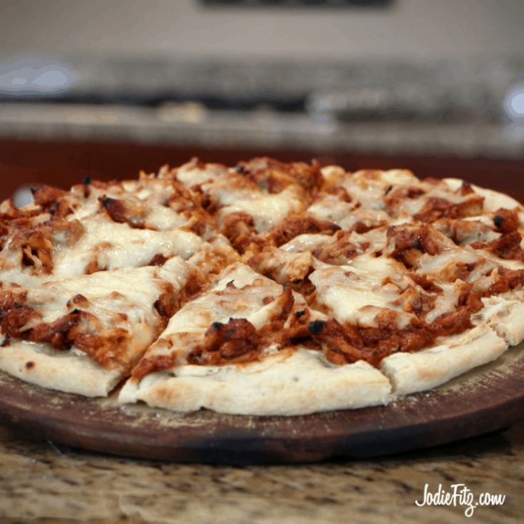 A bbq flavored turkey pizza on a pizza stone fully baked with leftover turkey, bbq sauce cheese and dough