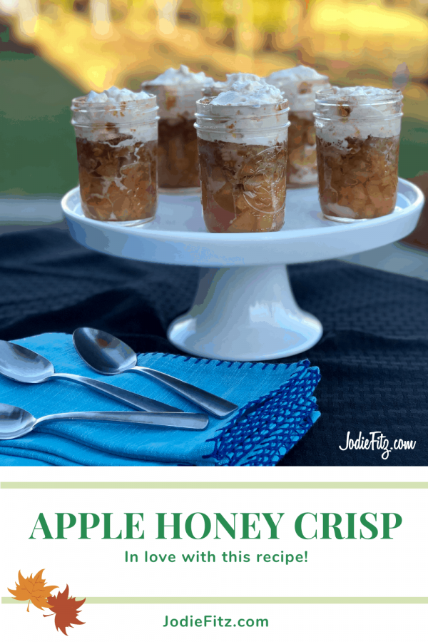 Apple Crisp topped with whipped cream in mason jars positioned on a cake platter