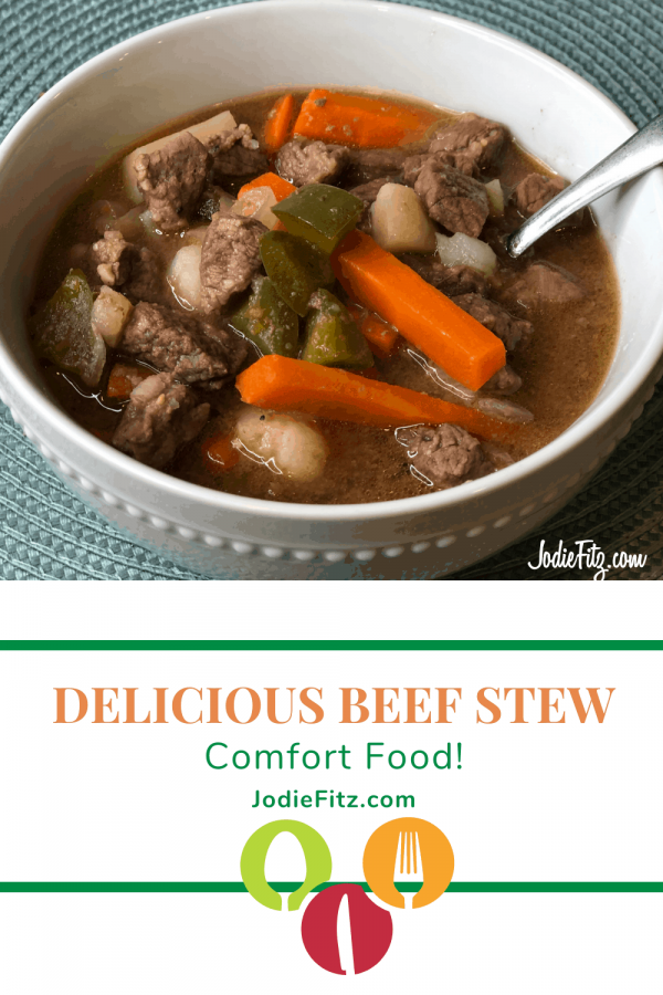 A bowl of beef stew with green bell peppers, potatoes and carrots in a white bowl