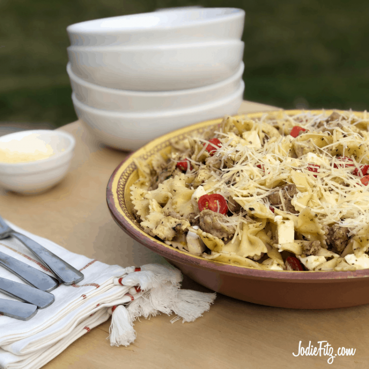 Bowl of Farfelle pasta tossed with fresh mozzarella, fresh tomatoes, sausage and chicken with pesto sauce and fresh shredded parmesan cheese on a table ready to be served