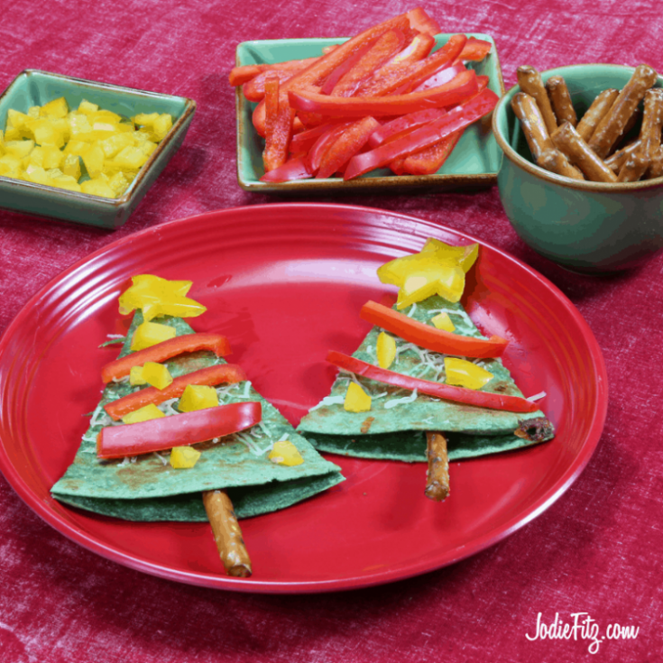 Spinach Wrap Quesadilla wedges that look like a Christmas Tree with a pretzel stick at the bottom and strips of red peppers to serve as garland and diced yellow peppers as ornaments