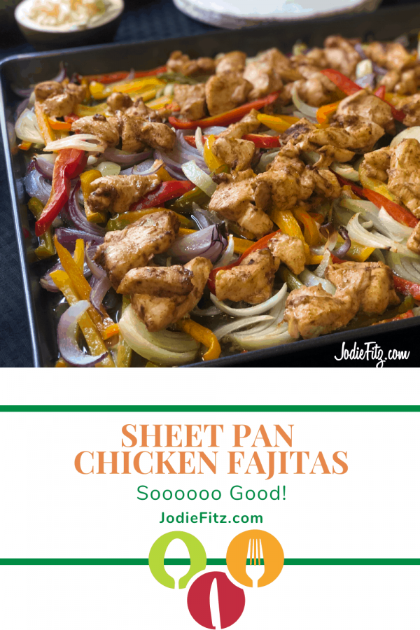 Sheet pan chicken fajitas on a baking sheet cooked with sweet onions, red onions and red, green, yellow and orange bell peppers