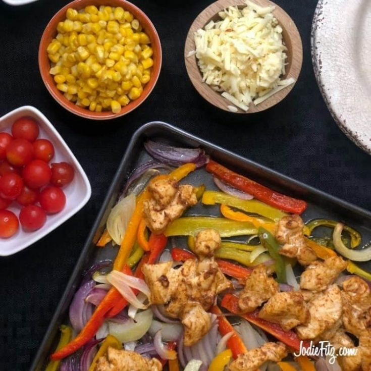Sheet pan chicken fajitas on a baking sheet cooked with sweet onions, red onions and red, green, yellow and orange bell peppers with grape tomatoes, cooked corn, shredded cheese, rice and avocados for serving