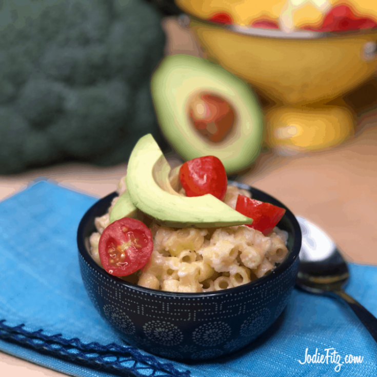 Bowl of macaroni and cheese in a small bowl topped with fresh tomatoes and avocados in a navy bowl
