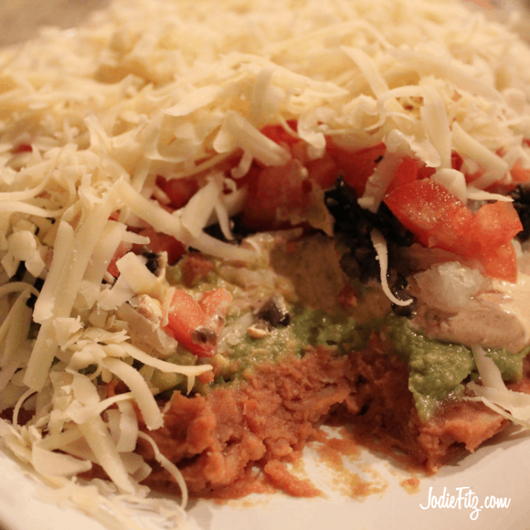 Taco Tower layered dip with refried beans, homemade guacamole, seasoned sour cream, finely chopped onions, chopped olives, fresh chopped tomatoes and shredded cheese